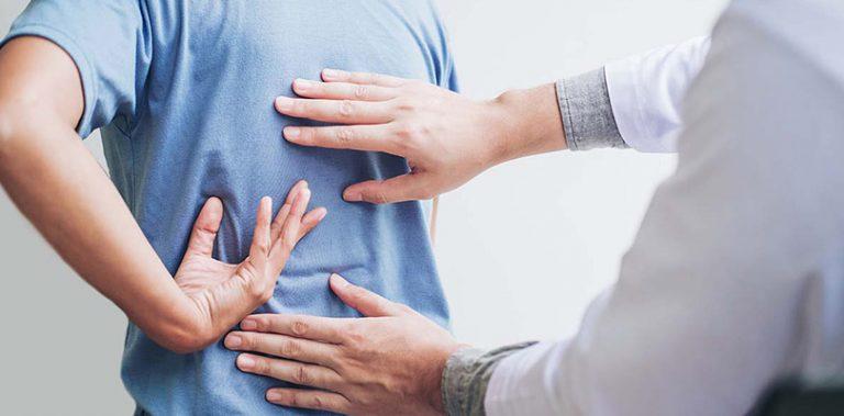Doctor examining man's back pain