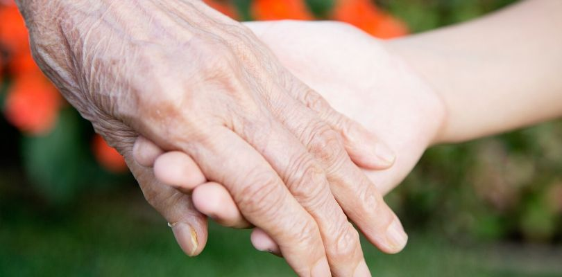 An old person holding a young family member's hand.