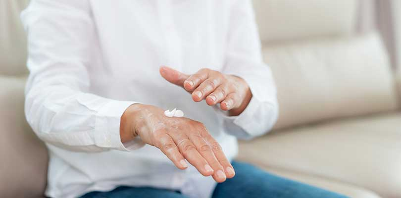 A woman putting topical cream on her hands.